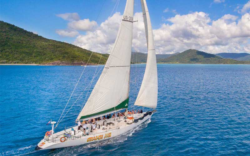 Spank Me Whitsundays with guests on top deck sailing to the islands